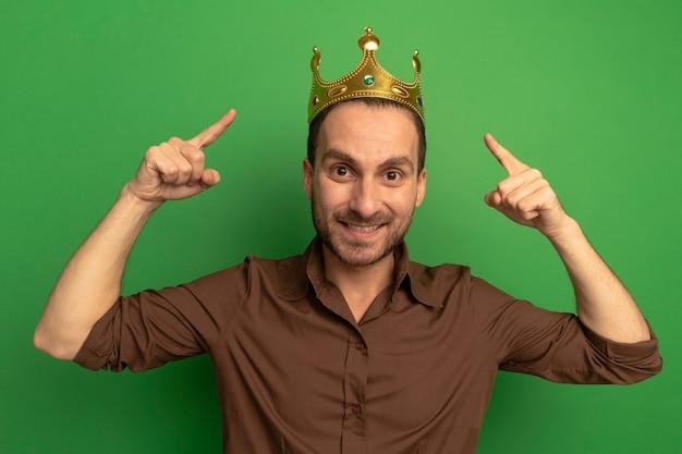 Lächelnder junger kaukasischer mann, der krone trägt, die auf kamera lokalisiert auf grünem hintergrund zeigt