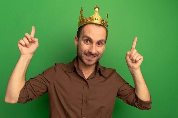 Lächelnder junger kaukasischer mann, der krone trägt, die oben auf grüner wand zeigt