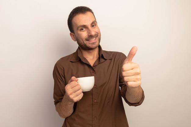 Lächelnder junger kaukasischer mann, der tasse tee hält und kamera betrachtet, die daumen oben auf weißem hintergrund mit kopienraum zeigt