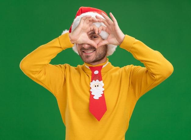 Lächelnder junger kaukasischer mann, der weihnachtshut und krawatte trägt und kamera betrachtet, die herzzeichen vor auge lokalisiert auf grünem hintergrund tut