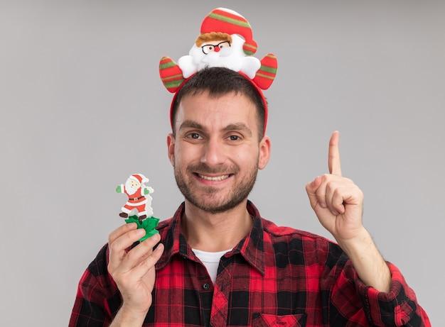 Lächelnder junger kaukasischer mann, der weihnachtsmann-stirnband hält, der schneemann-weihnachtsspielzeug hält, das kamera zeigt, die oben auf weißem hintergrund zeigt
