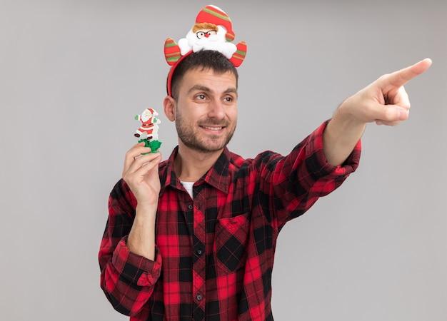 Lächelnder junger kaukasischer mann, der weihnachtsmann-stirnband hält, der schneemann-weihnachtsspielzeug hält und auf seite lokalisiert auf weißem hintergrund zeigt
