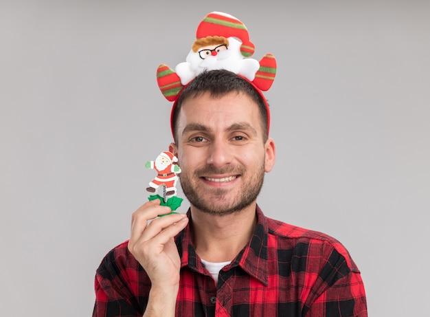 Lächelnder junger kaukasischer mann, der weihnachtsmann-stirnband hält schneemann-weihnachtsspielzeug, das kamera lokalisiert auf weißem hintergrund hält