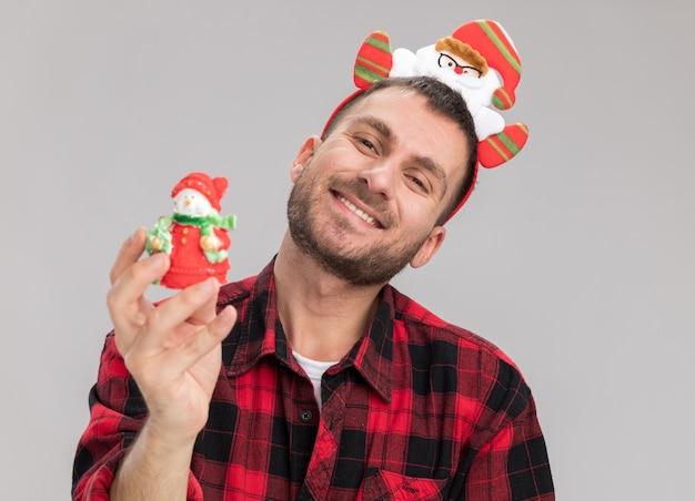Lächelnder junger kaukasischer mann, der weihnachtsmannclaus-stirnband hält schneemann-weihnachtsverzierung, die kamera lokalisiert auf weißem hintergrund hält