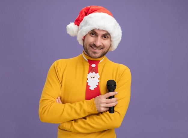 Lächelnder junger kaukasischer mann mit weihnachtsmütze und krawatte, der mit geschlossener haltung steht und das mikrofon hält, das isoliert auf lila wand mit kopienraum aussieht?