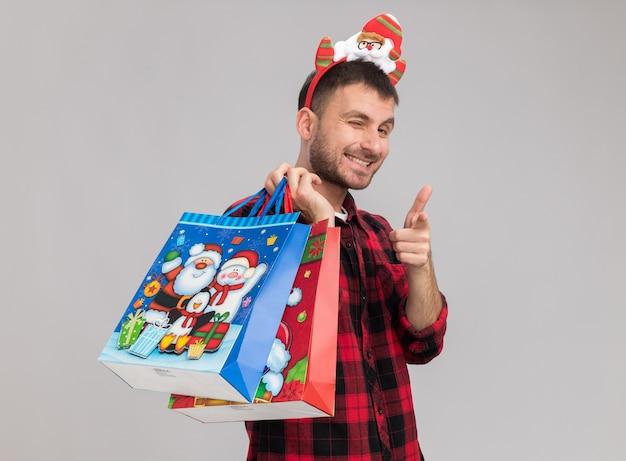 Lächelnder junger kaukasischer mann mit weihnachtsstirnband, der in der profilansicht steht und weihnachtsgeschenktüten auf der schulter hält und augenzwinkernd auf weiße wand mit kopienraum zeigt?