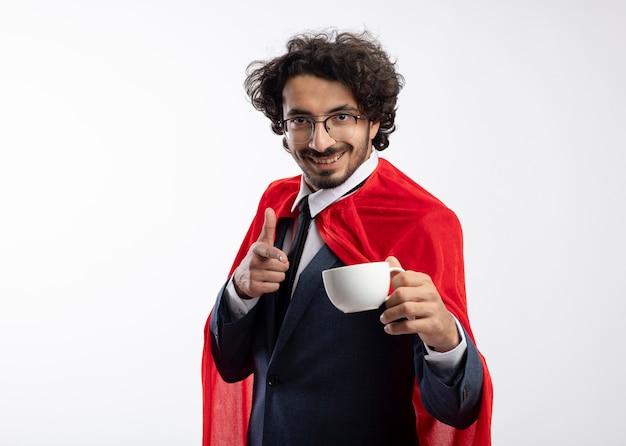 Lächelnder junger kaukasischer superhelden-mann in optischer brille mit anzug mit rotem umhang hält und zeigt auf tasse