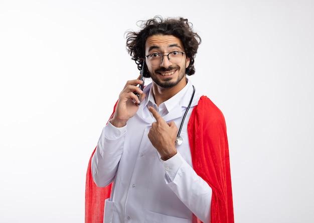 Lächelnder junger kaukasischer superheldenmann in der optischen brille, die arztuniform mit rotem umhang und mit stethoskop um den hals tragend zeigt und am telefon mit kopienraum spricht