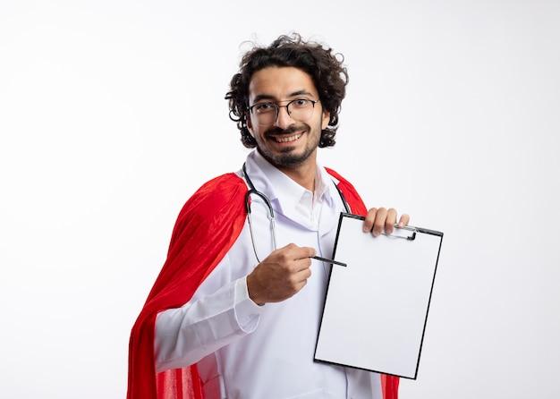 Lächelnder junger kaukasischer superheldenmann in der optischen brille, die arztuniform mit rotem umhang und mit stethoskop um hals hält, hält und zeigt auf zwischenablage mit bleistift