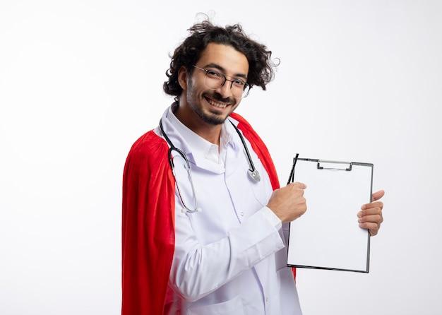 Lächelnder junger kaukasischer superheldenmann in der optischen brille, die arztuniform mit rotem umhang und mit stethoskop um halspunkte an der zwischenablage hält, die bleistift mit kopienraum hält