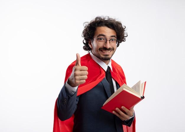 Lächelnder junger kaukasischer superheldenmann in optischer brille, der anzug mit rotem mantel trägt, hält buch und daumen hoch