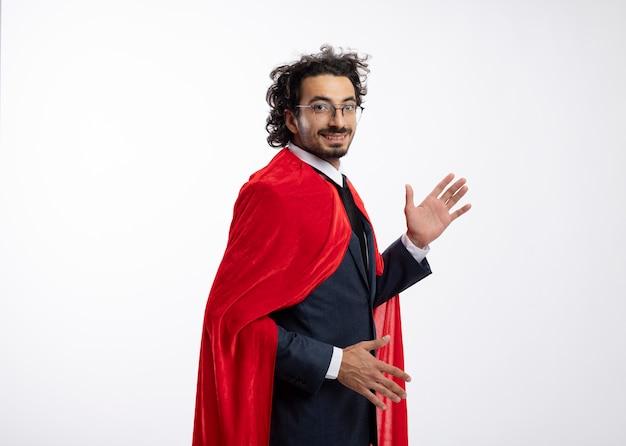 Lächelnder junger kaukasischer superheldenmann in optischer brille, der anzug mit rotem mantel trägt, steht seitlich mit erhobenen händen, die in die kamera blicken