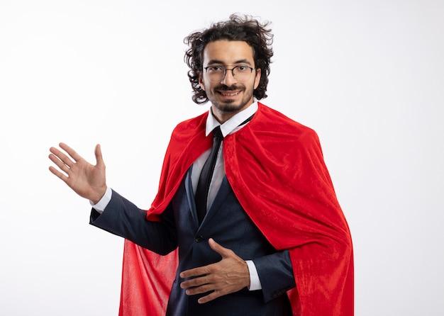 Lächelnder junger kaukasischer superheldenmann in optischer brille, der anzug mit rotem mantel trägt, steht seitlich mit erhobener hand