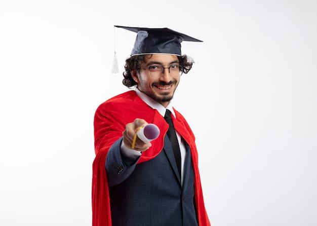 Lächelnder junger kaukasischer superheldenmann in optischer brille, der anzug mit rotem mantel und abschlusskappe trägt, hält diplom aus