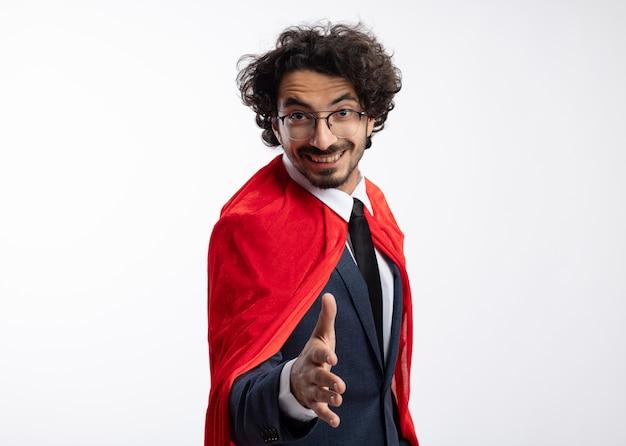 Lächelnder junger kaukasischer superheldenmann in optischer brille, der anzug mit rotem umhang trägt, streckt die hand aus