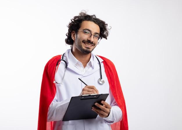Lächelnder junger kaukasischer superheldenmann in optischer brille, der eine arztuniform mit rotem umhang und mit stethoskop um den hals trägt, hält bleistift und zwischenablage