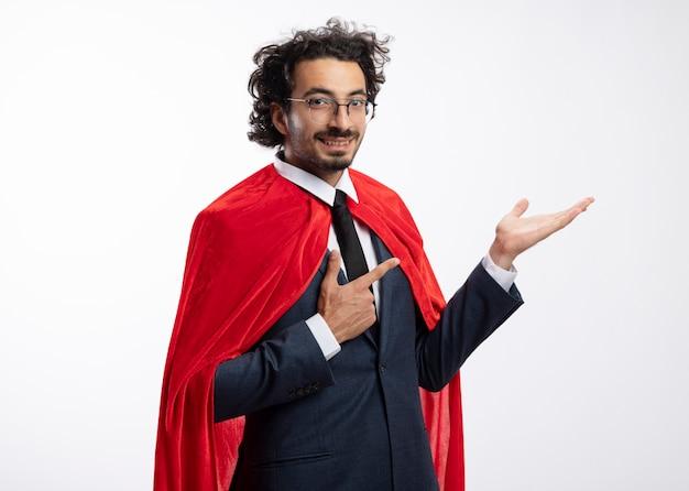 Lächelnder junger kaukasischer superheldenmann in optischer brille mit anzug mit roten umhangpunkten an leerer hand