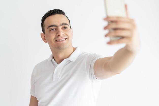 Lächelnder junger kerl, der selfie foto auf smartphone macht