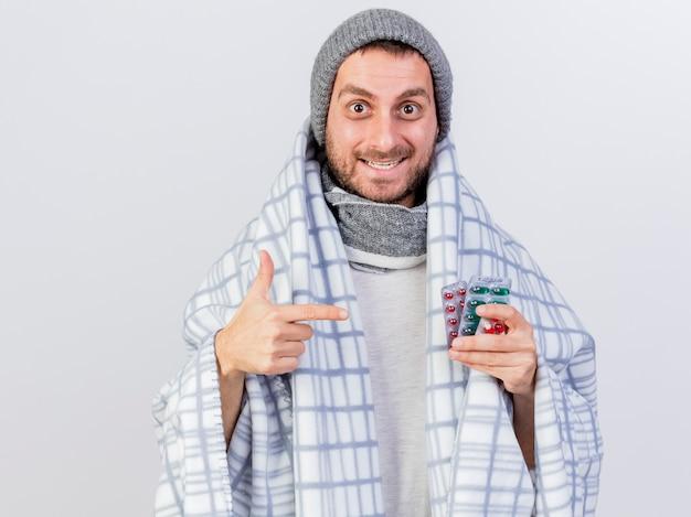 Lächelnder junger kranker mann, der wintermütze und schal trägt, die im karierten halten eingewickelt sind und auf pillen zeigen, die auf weiß isoliert werden