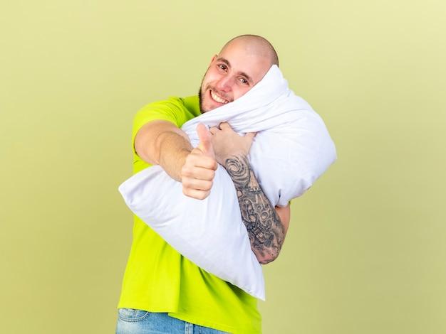 Lächelnder junger kranker mann hält kissen und daumen isoliert auf olivgrüner wand