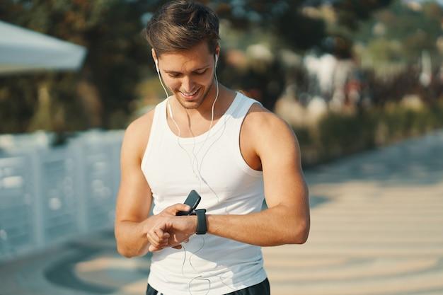 Lächelnder junger laufender mann, der seinen herzfrequenzmonitor sport-smartwatch betrachtet. verbesserung seiner ergebnisse.