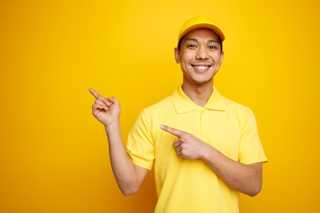 Lächelnder junger lieferbote, der mütze und uniform trägt, zeigt an ecke