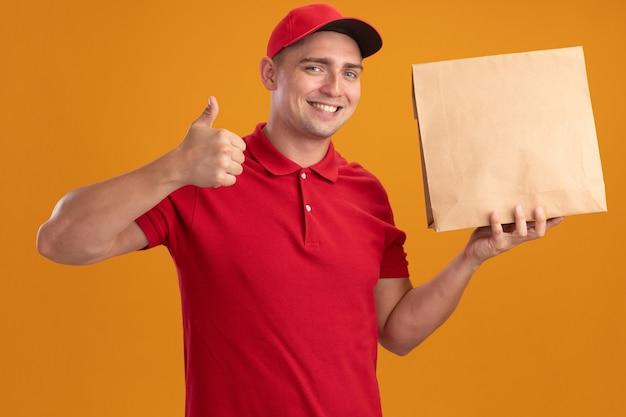 Lächelnder junger lieferbote, der uniform mit kappe hält, die papiernahrungsmittelpaket hält, das daumen oben auf orange wand lokalisiert zeigt