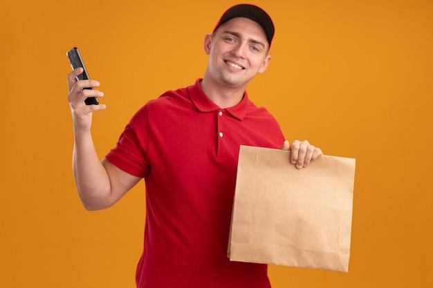 Lächelnder junger lieferbote, der uniform mit kappe hält, die papiernahrungsmittelpaket mit telefon lokalisiert auf orange wand hält
