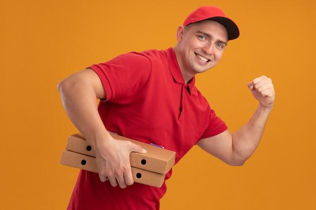 Lächelnder junger lieferbote, der uniform mit kappe hält, die pizzakästen hält, die starke geste lokalisiert auf orange wand zeigt