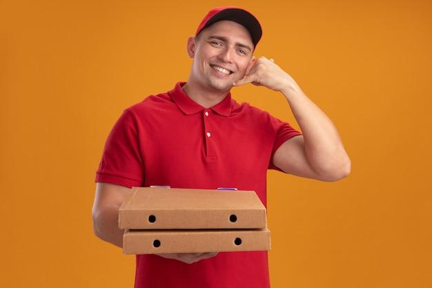 Lächelnder junger lieferbote, der uniform mit kappe hält, die pizzakästen hält, die telefonanrufgeste lokalisiert auf orange wand zeigt
