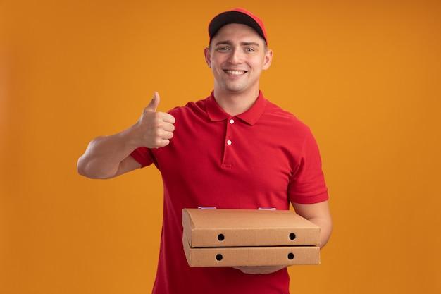 Lächelnder junger lieferbote, der uniform mit kappe hält, die pizzaschachteln hält daumen oben auf orange wand lokalisiert