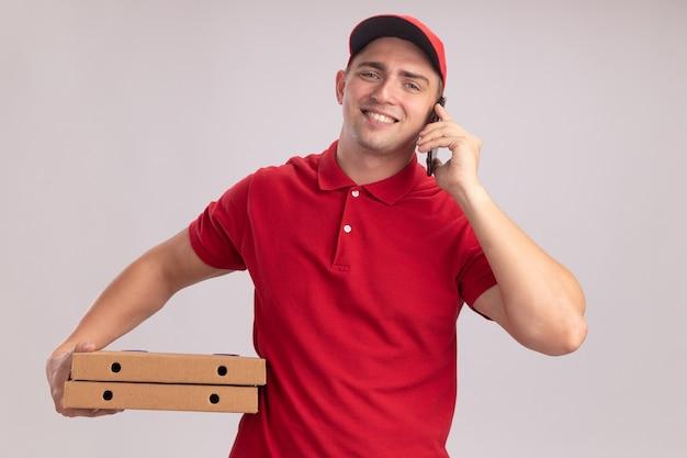 Lächelnder junger lieferbote, der uniform mit kappe hält, die pizzaschachteln hält und am telefon lokalisiert auf weißer wand spricht