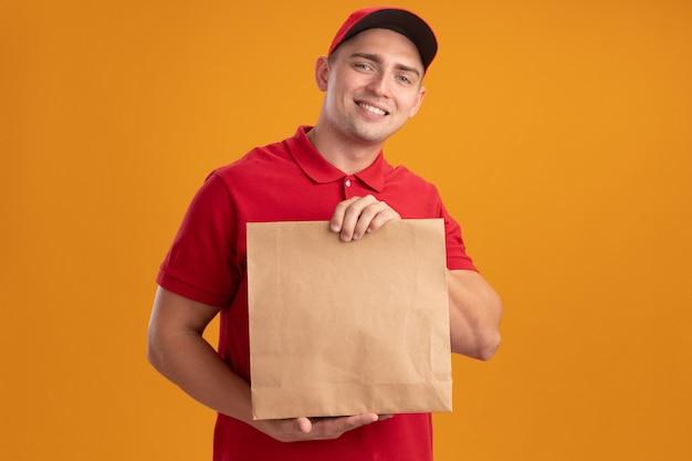 Lächelnder junger lieferbote, der uniform mit kappe hält papiernahrungsmittelpaket lokalisiert auf orange wand trägt