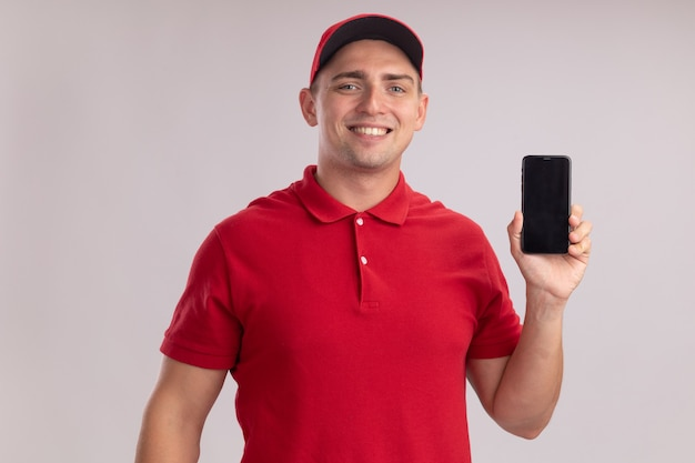 Lächelnder junger lieferbote, der uniform mit kappe hält telefon lokalisiert auf weißer wand trägt