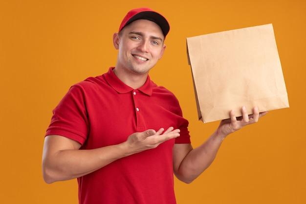 Lächelnder junger lieferbote, der uniform mit kappe hält und punkte mit hand an papiernahrungsmittelpaket lokalisiert auf orange wand trägt