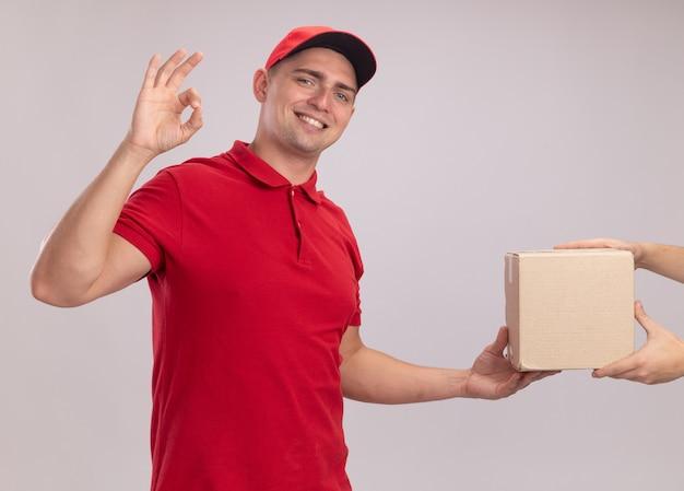 Lächelnder junger lieferbote, der uniform mit kappe trägt, die kasten zum kunden gibt, der okay geste zeigt, die auf weißer wand lokalisiert wird