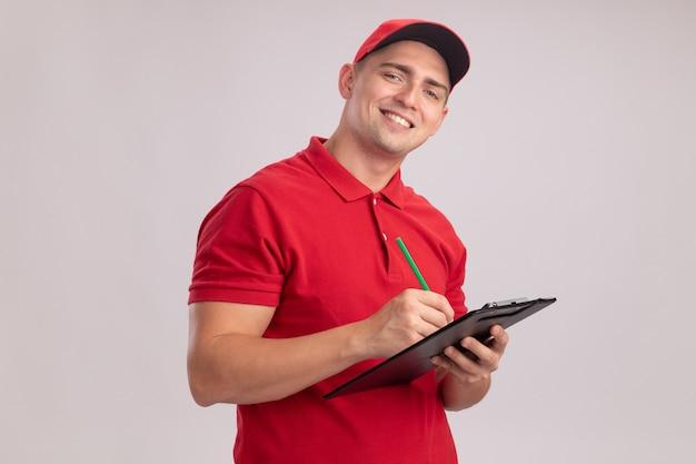 Lächelnder junger lieferbote, der uniform mit kappe trägt, schreibt etwas in zwischenablage lokalisiert auf weißer wand