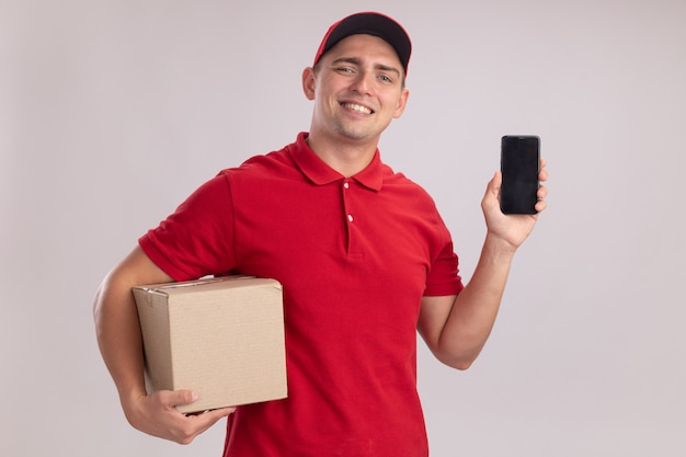 Lächelnder junger lieferbote, der uniform mit kastenhaltebox und telefon trägt, lokalisiert auf weißer wand