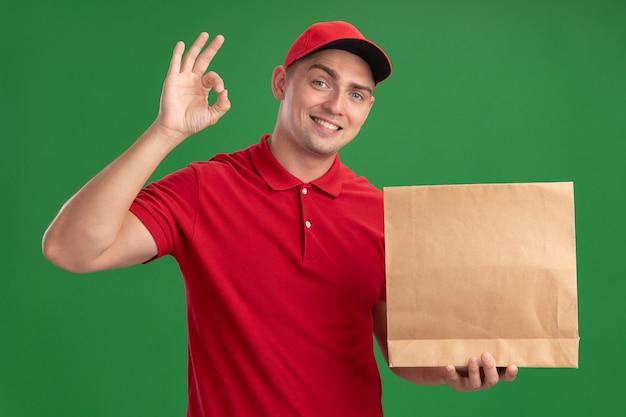 Lächelnder junger lieferbote, der uniform und kappe hält, die papiernahrungsmittelpaket hält, das okay geste lokalisiert auf grüner wand zeigt