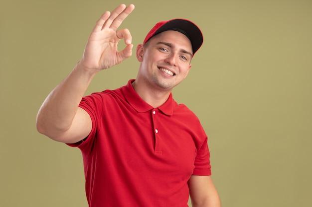 Lächelnder junger lieferbote, der uniform und kappe trägt, die auf olivgrüne wand isolierte okay-geste zeigen