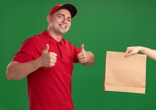 Lächelnder junger lieferbote, der uniform und kappe trägt, die dem kunden papiernahrungsmittelpaket geben, das daumen oben isoliert auf grüner wand zeigt