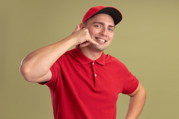 Lächelnder junger lieferbote, der uniform und kappe trägt, die telefonanrufgeste lokalisiert auf olivgrüner wand zeigt