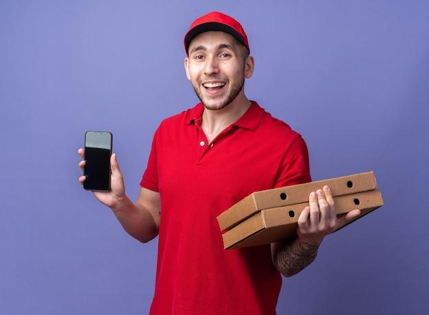 Lächelnder junger lieferbote in uniform mit mütze, der pizzakartons mit telefon hält