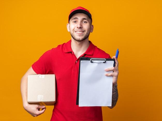 Lächelnder junger lieferbote in uniform mit mütze mit box mit zwischenablage