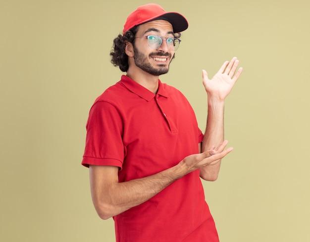Lächelnder junger liefermann in roter uniform und mütze mit brille, der mit der hand an der seite nach vorne zeigt, isoliert auf olivgrüner wand mit kopierraum