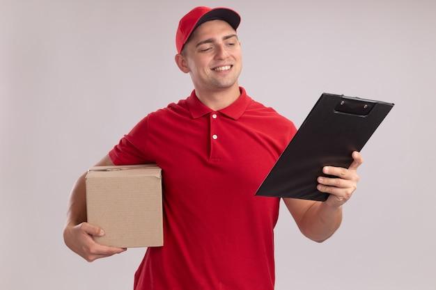 Lächelnder junger liefermann in uniform mit mütze, der eine schachtel hält und die zwischenablage in seiner hand isoliert auf weißer wand betrachtet