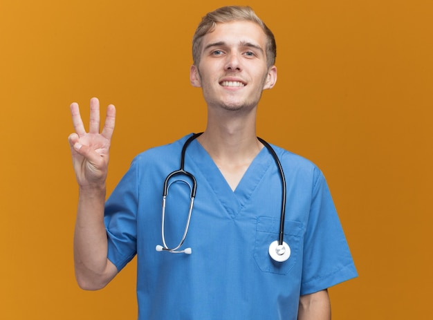 Lächelnder junger männlicher arzt, der arztuniform mit stethoskop trägt, das drei auf orange wand lokalisiert zeigt
