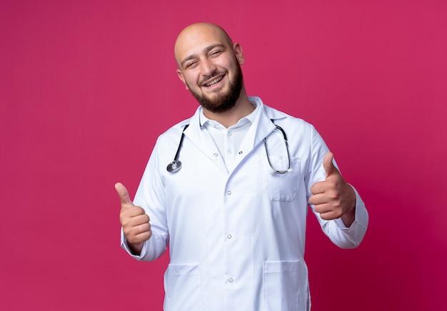 Lächelnder junger männlicher arzt, der medizinische robe und stethoskop seine daumen hoch auf rosa isoliert trägt