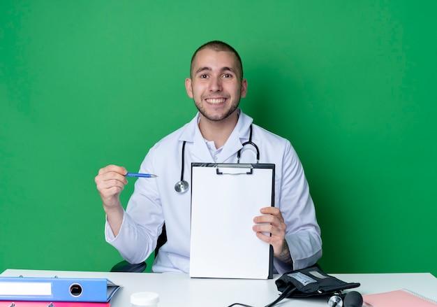 Lächelnder junger männlicher arzt, der medizinische robe und stethoskop trägt, die am schreibtisch mit arbeitswerkzeugen sitzen und mit stift auf zwischenablage lokalisiert auf grüner wand zeigen
