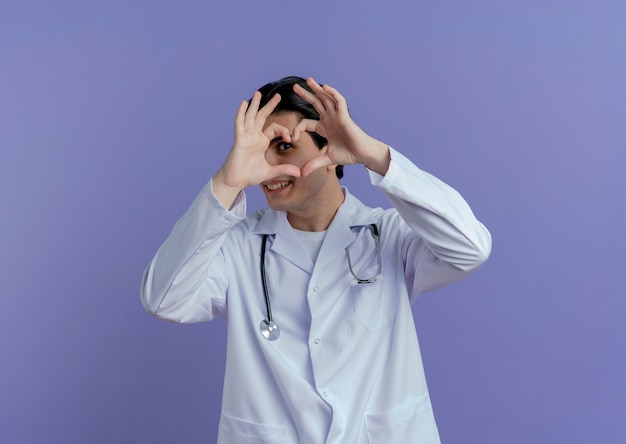 Lächelnder junger männlicher arzt, der medizinische robe und stethoskop trägt, die herzzeichen tun, das durch sie isoliert schaut